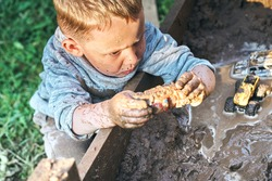 Cute serious preschooler boy with dirty face and clothes playing with toy cars in the sandbox near wooden rural house in summer day in countryside