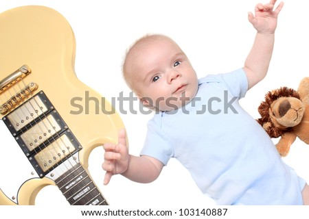 Cute seven week old newborn baby laying with a guitar and toy - stock photo