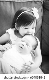 stock photo of cute siblings toddler girl and newborn baby together