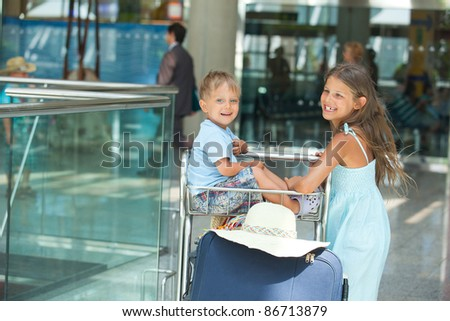 Cute sister and brother in the airport with trolley baggage