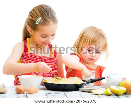 Stock Photo cute sisters cooking pancakes on kitchen isolated on a white background