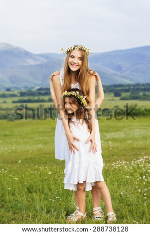 Cute sisters girls are wearing white dresses at  green camomile field with mountains view