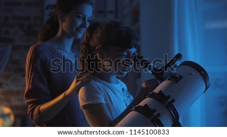 Cute sisters watching the stars together at home using a telescope, family and leisure concept