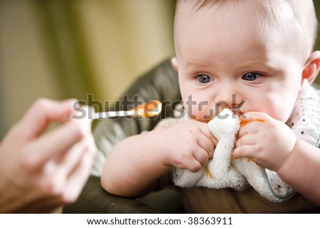 Cute six month old baby being fed, staring at baby food on spoon