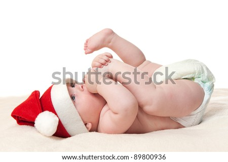 cute six month old baby boy in christmas hat playing with his feet, isolated on white background