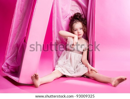 cute six year old girl as an alive doll in the pink box, against pink studio background