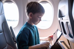 Cute six years old boy, playing on tablen in aircraft on boar, traveling on vacation with parents and siblings.