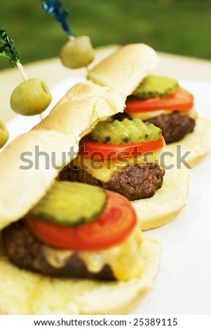 Cute sliders with olive garnish at an outdoor dinner party.