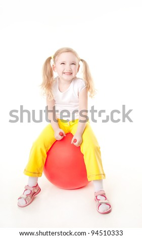 cute sly little girl doing gymnastic exercise with ball