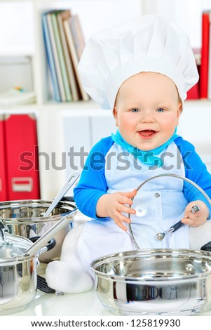 Cute small baby in the cook costume at the kitchen.