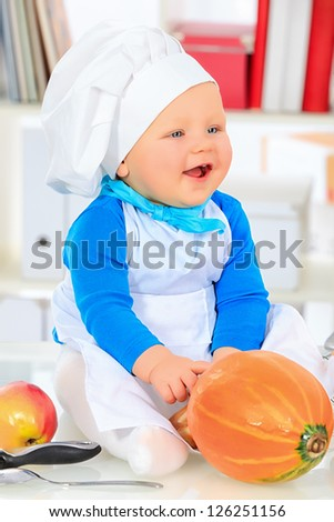 Cute small baby in the cook costume sitting with a fresh pumpkin at the kitchen.