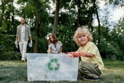 Cute small boy sitting near recycle bin and smiling at camera while collecting plastic waste in forest or park with young happy parents eco activists. Environmental conservation and ecology concept