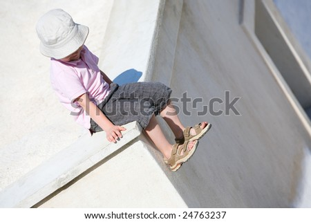 Cute small boy sitting on rooftop of white house