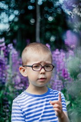 Cute small boy with glasses posing at the beautiful summer background of wild lupines flowers. Kid shows index finger up gesture - wants to ask or say something. Artistic bokeh.