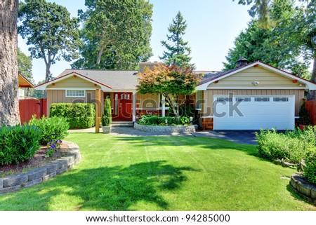 Cute small brown rambler house with red door and white garage door