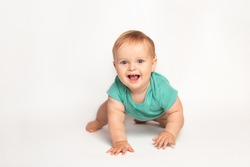 Cute small caucasian toddler baby boy child crawl on white studio floor. Smiling little infant kid wearing a green t-shirt explore world. Childcare and upbringing concept.