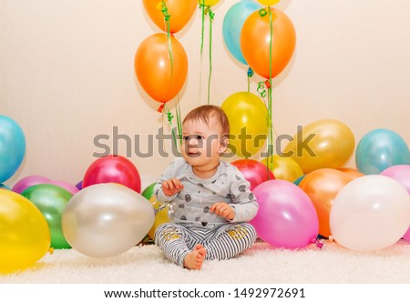 Cute small child with balloons, celebrates holiday. Children and celebration concept.