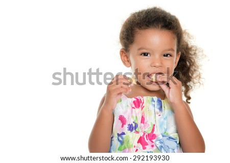 Cute small girl eating a cookie isolated on white