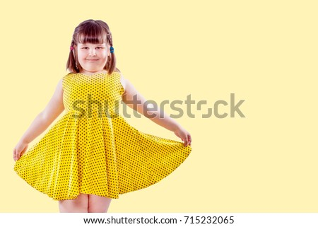 cute small girl in yellow on pale yellow background with copy space #715232065