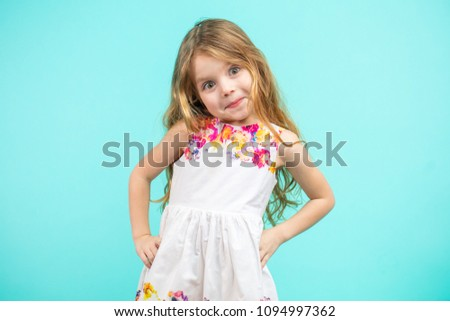 af29c97731a54 Cute small girl wearing a flowers summer dress with arms akimbo isolated on  blue #1094997362