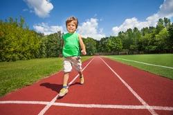 Cute small smiling boy runs slowly on the marathon road of stadium