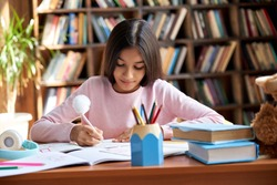 Cute smart hispanic indian preteen kid girl student, latin child primary school pupil studying at table, doing homework at home, writing task, taking notes, learning sitting at classroom desk.