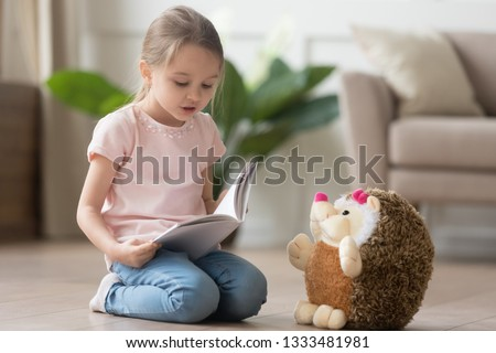 Photo of Cute smart little kid girl playing alone reading story to fluffy hedgehog sitting on warm floor at home, funny creative preschool small child holding book teaching toy, children imagination education