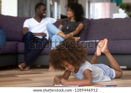 Cute smart mixed race child girl playing drawing with colored pencils on warm heated floor with happy african parents relax on couch in living room, kid daughter have fun, black family time at home