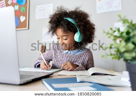 Cute smiling african school kid girl wearing headphones virtual distance learning online listening remote education digital class doing homework studying at home classroom sitting at desk with laptop.