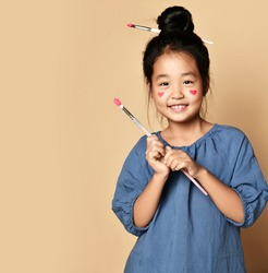 Cute smiling asian kid girl artist with painted red hearts on cheeks and with brush in hair and in hands over yellow wall background with copy space. Trendy children fashion, asian outfit concept
