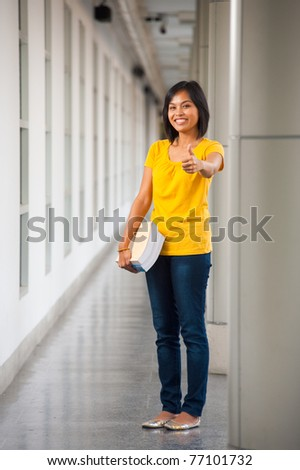 Cute smiling Asian student in yellow t-shirt, blue jeans holding books at side and giving thumbs up on a modern college campus gray hallway while looking at. 20s female Thai model of Chinese descent