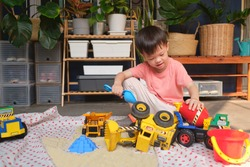 Cute smiling Asian 3 - 4 years old toddler boy playing with kinetic sand alone at home, Child playing with toy construction machinery, Montessori education, Creative play for kids concept