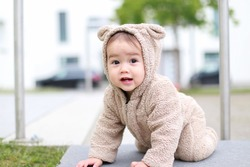 Cute smiling baby boy in teddy bear costume crawling outdoor park.mixed race Asian-German infant play and learn outside. Happy healthy child smile with first milk teeth.