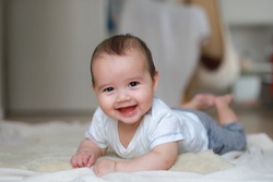 Cute smiling baby boy relaxing at home. Happy infant mixed race Asian-German about 5-6 months old crawling on the floor. Healthy newborn.