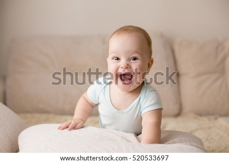 Cute smiling baby in blue bodysuit on a beige couch. #520533697