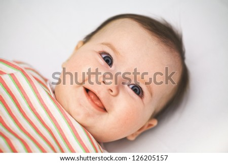 Cute smiling  baby with open blue eyes close up