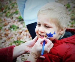 Cute smiling blond little boy in red coat getting his face painted a blue shark by face painting artist.