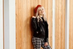 Cute smiling blonde girl in red beret, black leather jacket, checkered trousers, stylish fall outfit