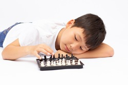 Cute smiling boy shows chess pieces on a chessboard on a white insulated background