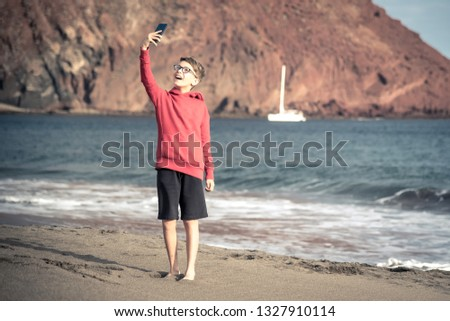 Cute smiling boy with glasses in a red hoodie taking a pic with phone at the beach enjoying holiday. Young male watching his mobile phone and enjoy the trip in a new exotic place. Selfie portrait