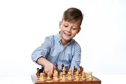 Cute smiling Caucasian boy shows chess pieces on a chessboard on a white insulated background