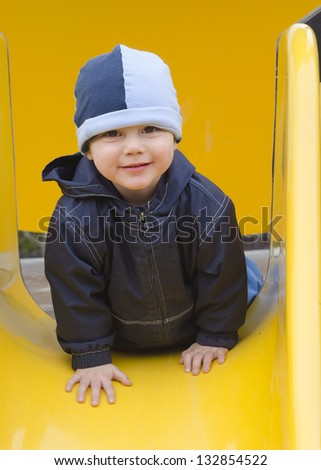 Cute smiling child, boy or girl, on the top of a slide in a children playground.
