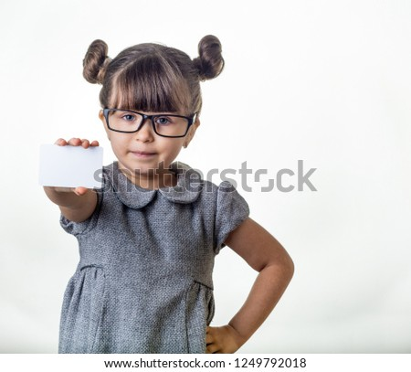 06b20b8a2f97 Cute smiling child with glasses holding discount white card in her hands.  Kid with credit