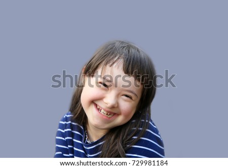 Cute smiling down syndrome girl on the blue background #729981184