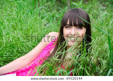 Cute smiling female lying on grass field at the park