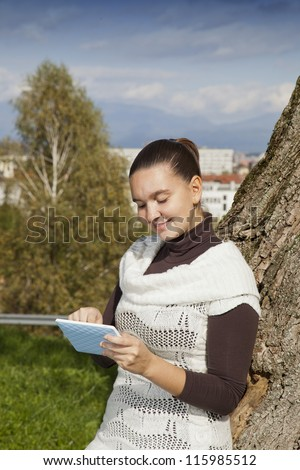 Cute smiling girl with modern tablet PC e-reader, outdoors in the park - stock photo