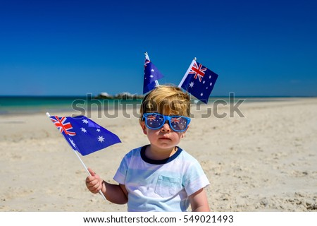 Cute smiling kid with Australian flags sitting on the sand at the beach on Australia Day #549021493