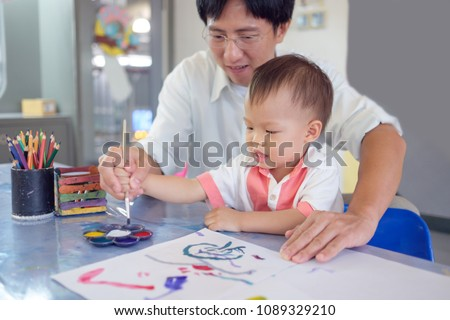 Cute smiling little Asian 18 months / 1 year old toddler baby boy child painting with brush and watercolors, Businessman father painting with son after working time, Creative play for toddlers concept #1089329210