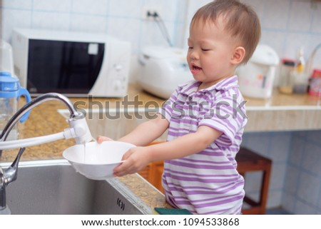 Cute smiling little Asian 2 year old toddler baby boy child standing and having fun doing the dishes / washing dishes in kitchen at home, Little home helper, chores for kids, child development concept