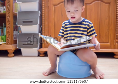 Cute smiling little Asian 2 years old toddler baby boy child is sitting on blue potty and reading book in living room at home, Potty training, Learning to use the Toilet for toddlers concept